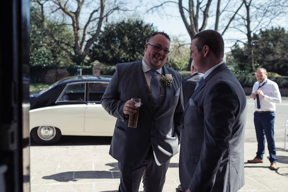 The groom and best man stand outside the wedding venue while the guests arrive.