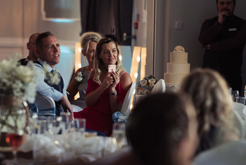Wedding guest sitting besides the cake sits and films the speeches on her phone