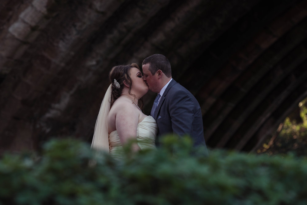 Partly hidden by a bush, the bride and groom share a kiss under a bridge
