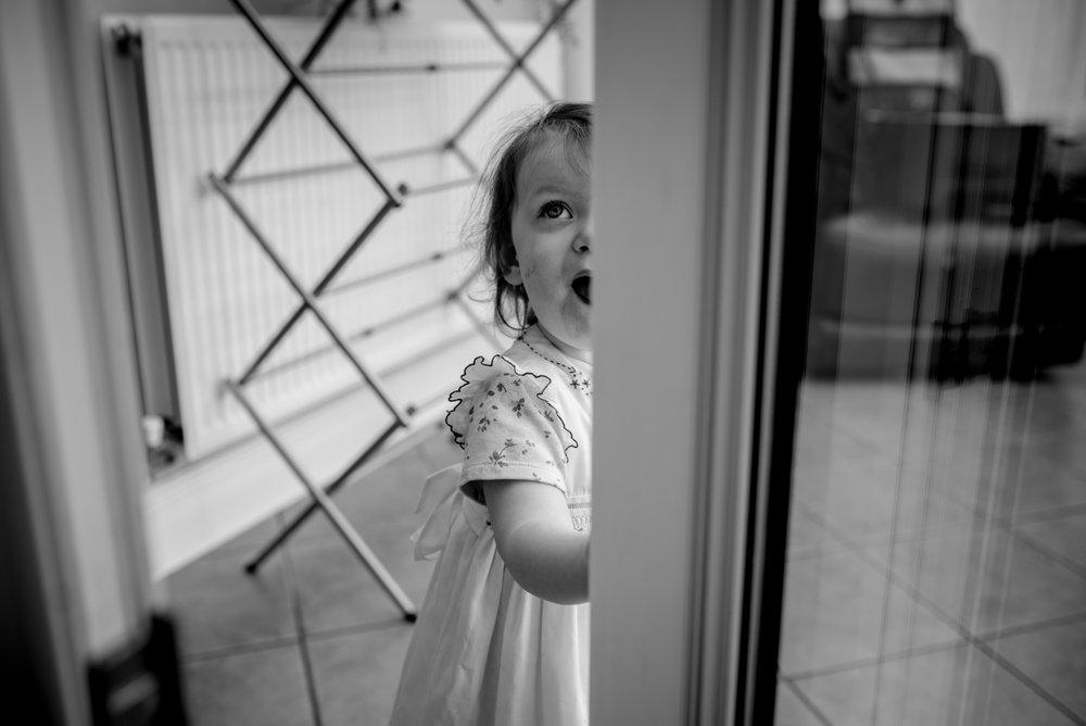 Young flower girl peeps through an open window