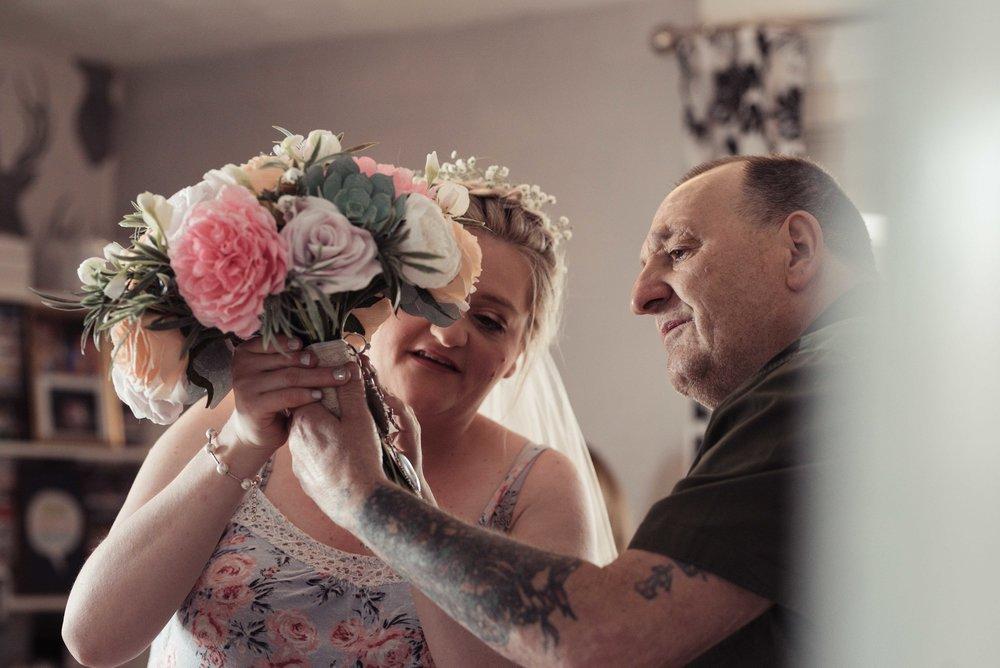 The bride shows her dad her wedding bouquet