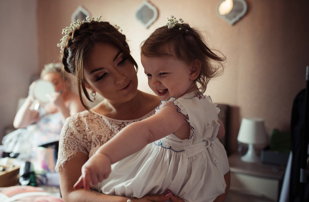 The flower girl and her mum standing in the bedroom