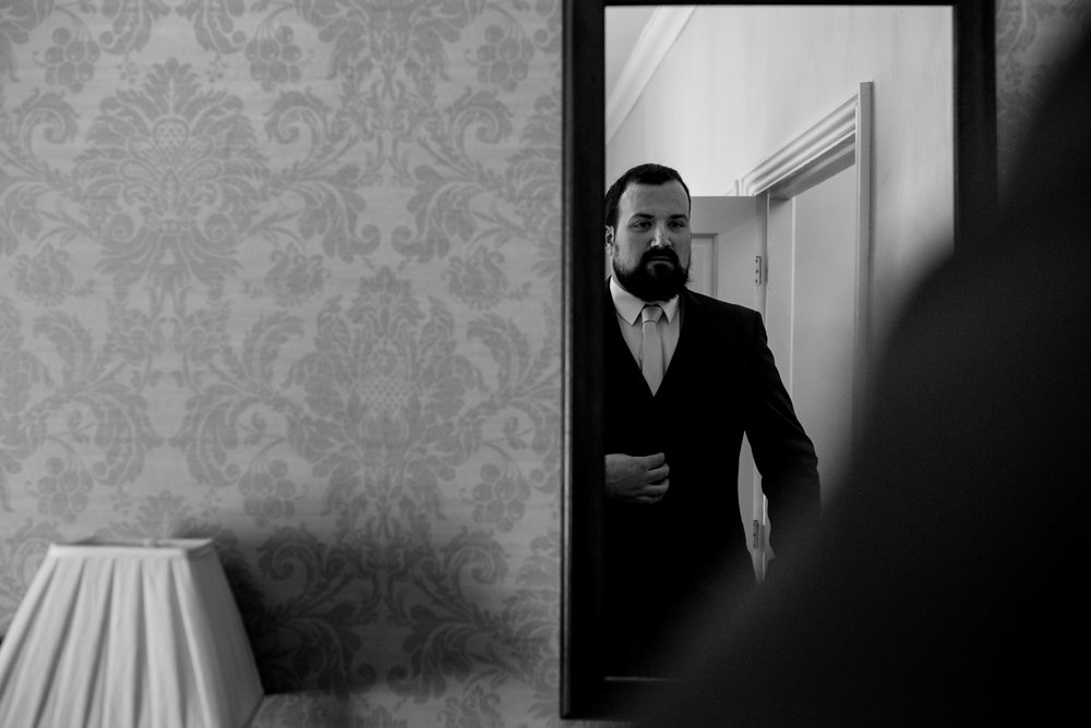 The groom checks himself out in the mirror before going downstairs to be married