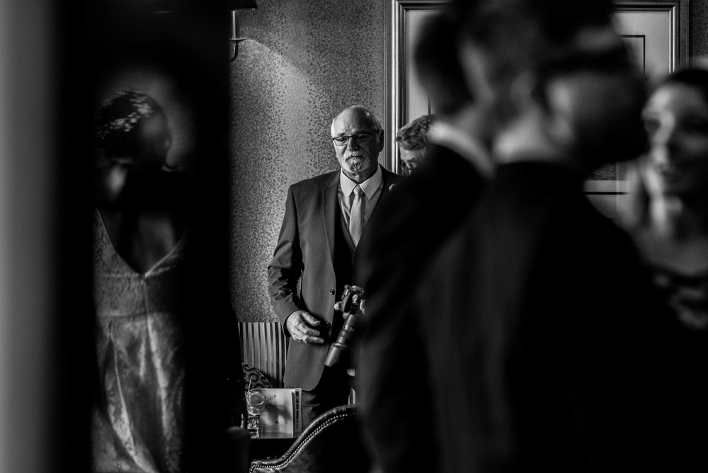 The father of the groom stands and waits for his son to come into the bar area of the wedding venue