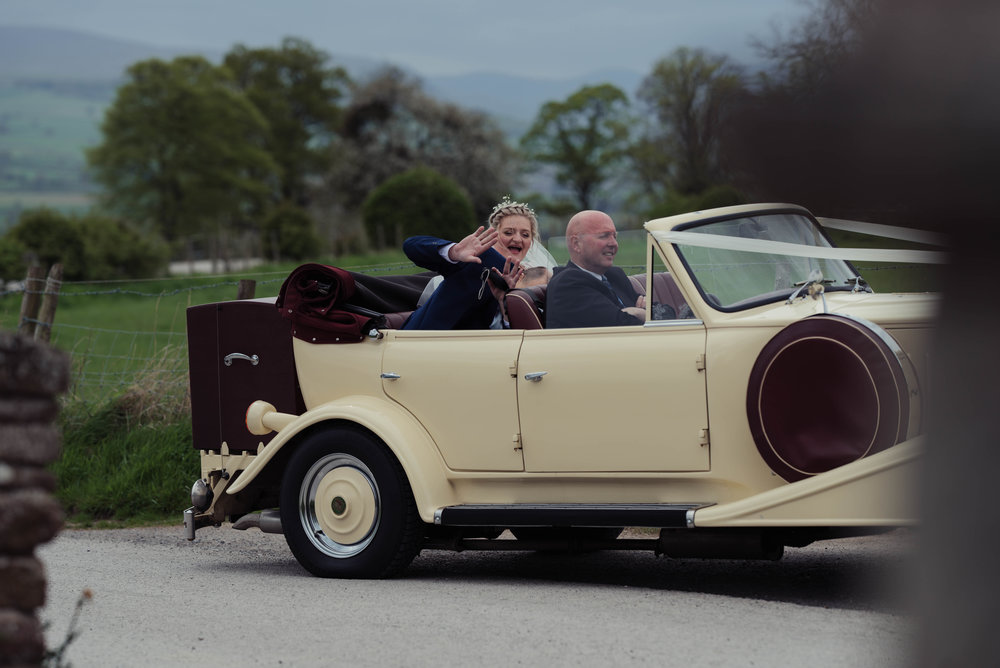 The bride and groom arrive at the wedding venue in a vintage car
