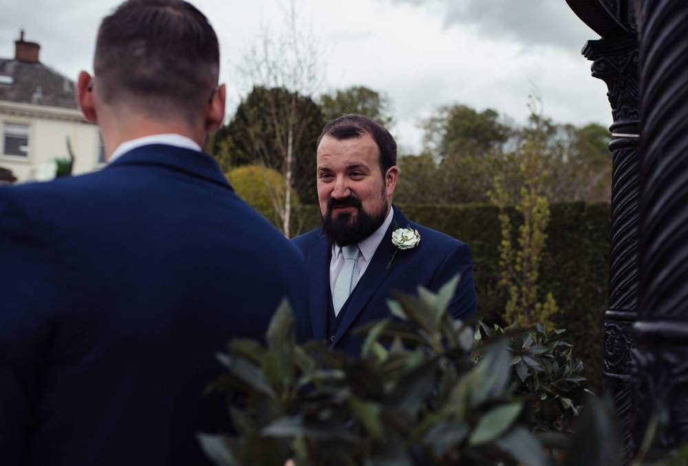 A nervous groom stands waiting for the bride to arrive
