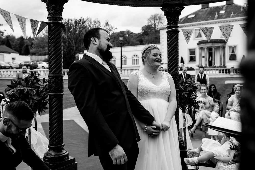 The bride and groom laugh out loud as they say their wedding vows together