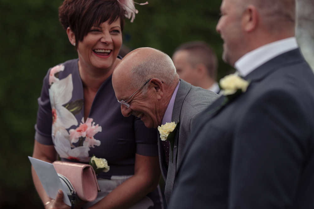 Two wedding guests literally laugh out loud together