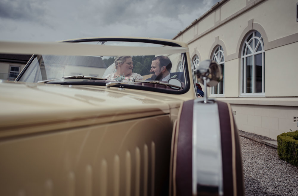 The bride and groom sit and share a moment alone together in their wedding car