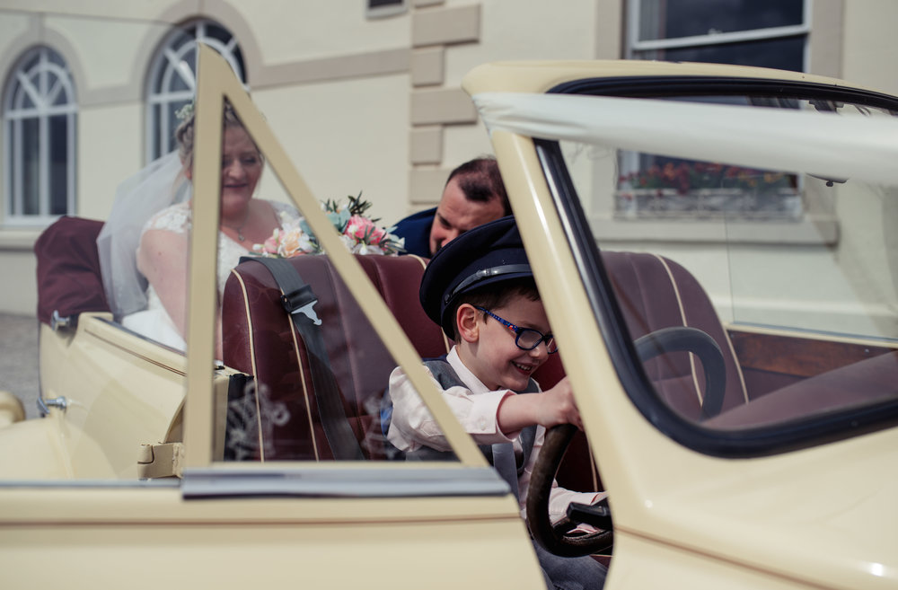 A page boys sits with a hat on in the drivers seat of the wedding car