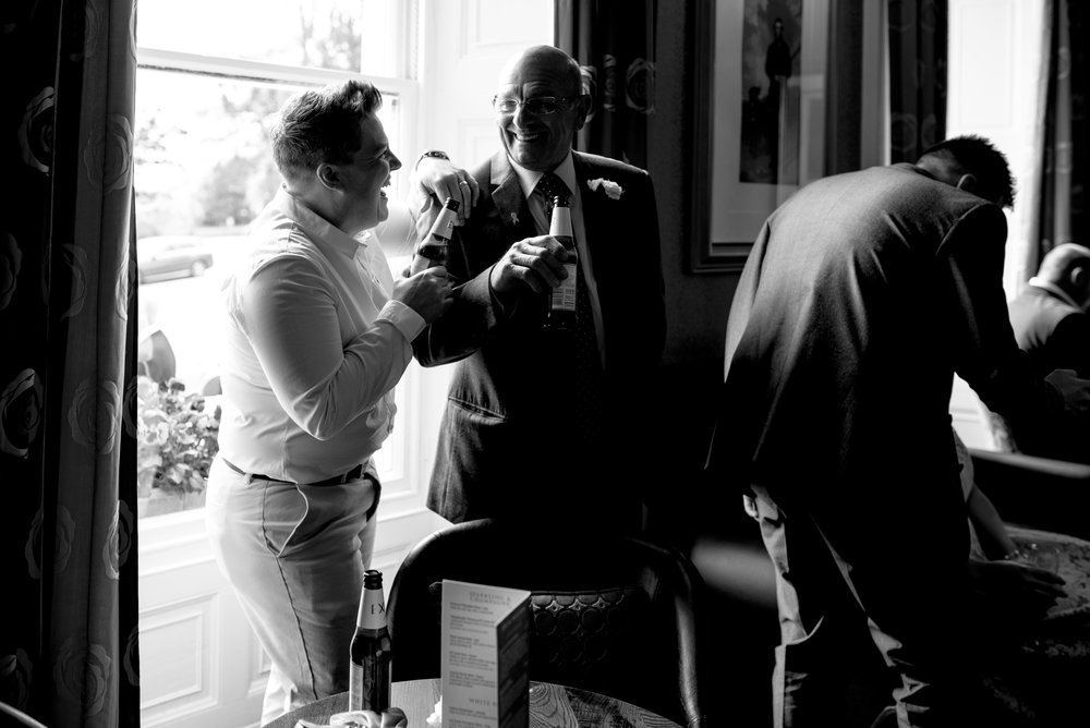 Two wedding guests stand by the window holding a drink and having a laugh