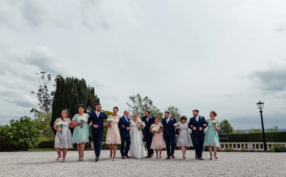 The bridal party stand together in a line and walk towards the camera outside the wedding venue