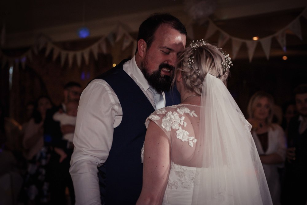 The bride and groom share a kiss during their first dance
