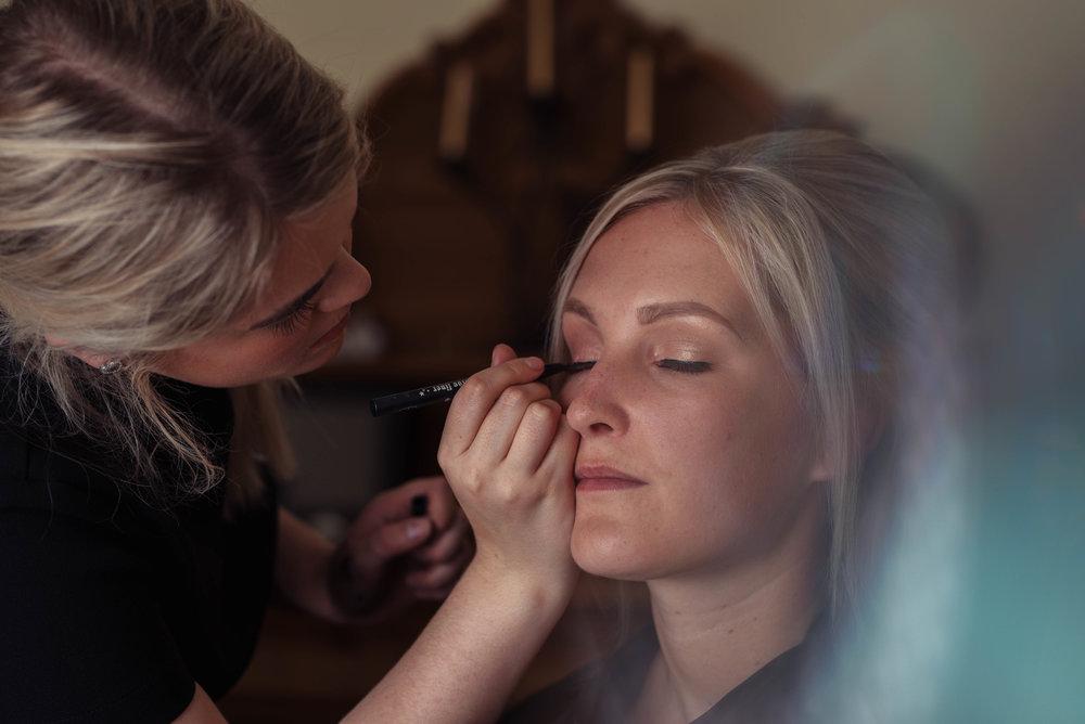 Sitting bride having her eye makeup finished
