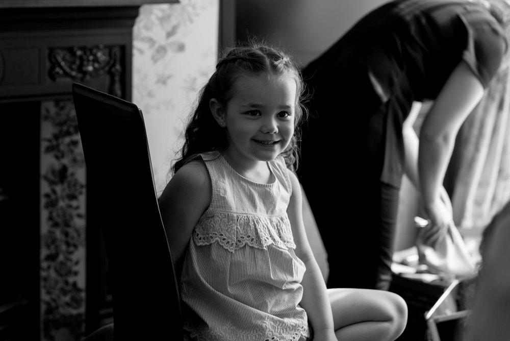 A flower girl smiles for the camera as she sits to have her wedding hair done