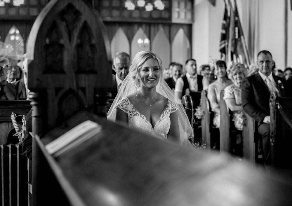 the bride has a little laugh to herself during the church service