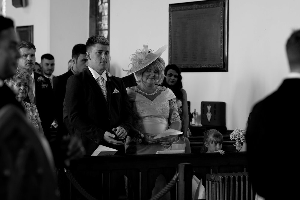 the brides mother and brother smile as they watch the wedding ceremony