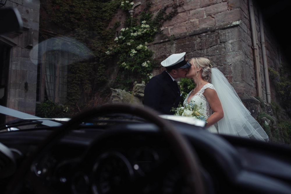 An aston martin provides the window through which the bride and groom can be seen kissing at askham hall
