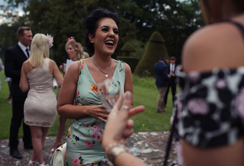 A wedding guest laughs out loud during the reception welcome drinks