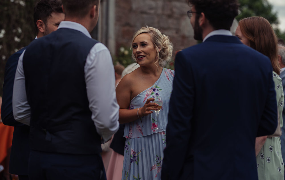 a lady dressed in a blue and white dress chats to a group of wedding guests