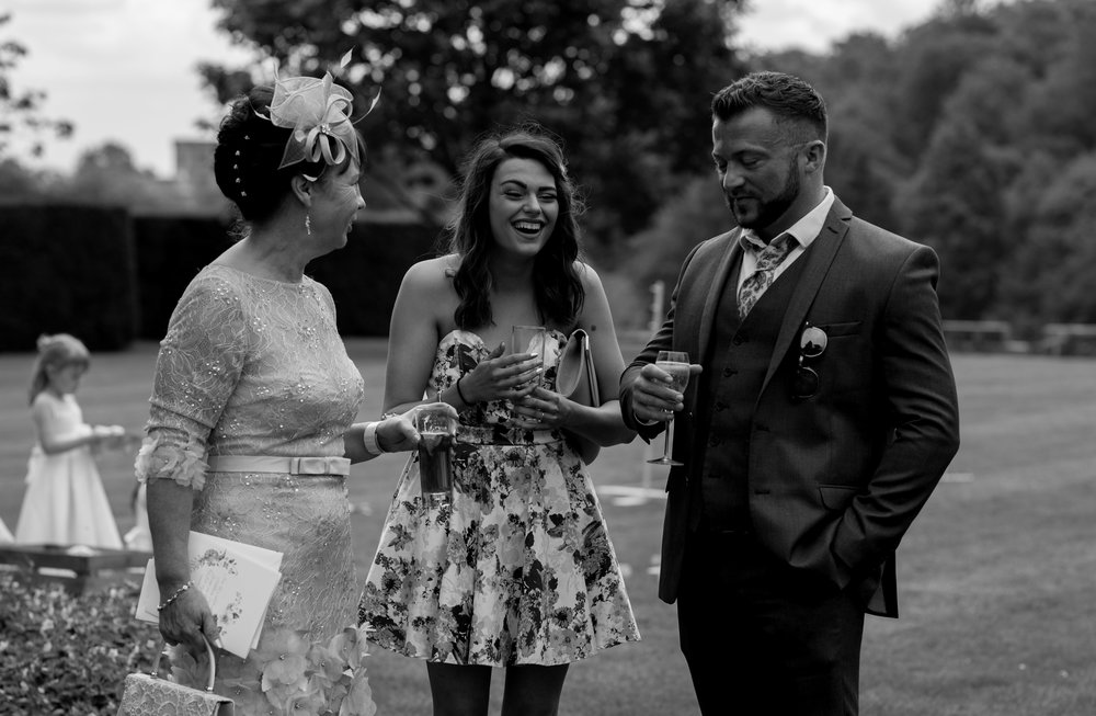 a girl in a short flowery dress laughs at a joke by one of the other wedding guests