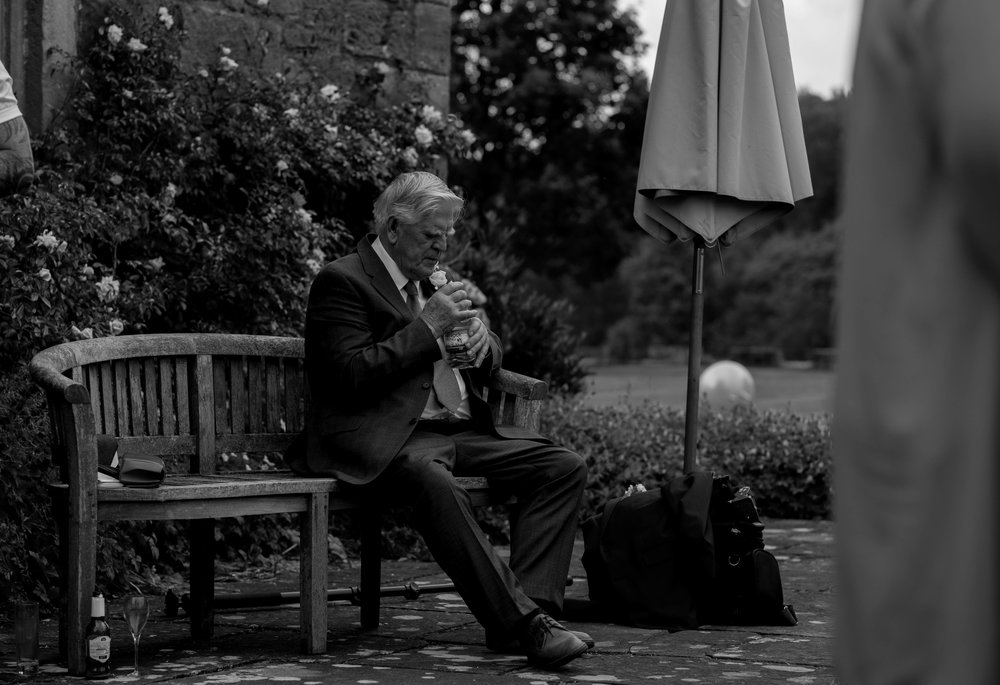 grandfather takes some time out on a bench outside askham hall to have a drink of water