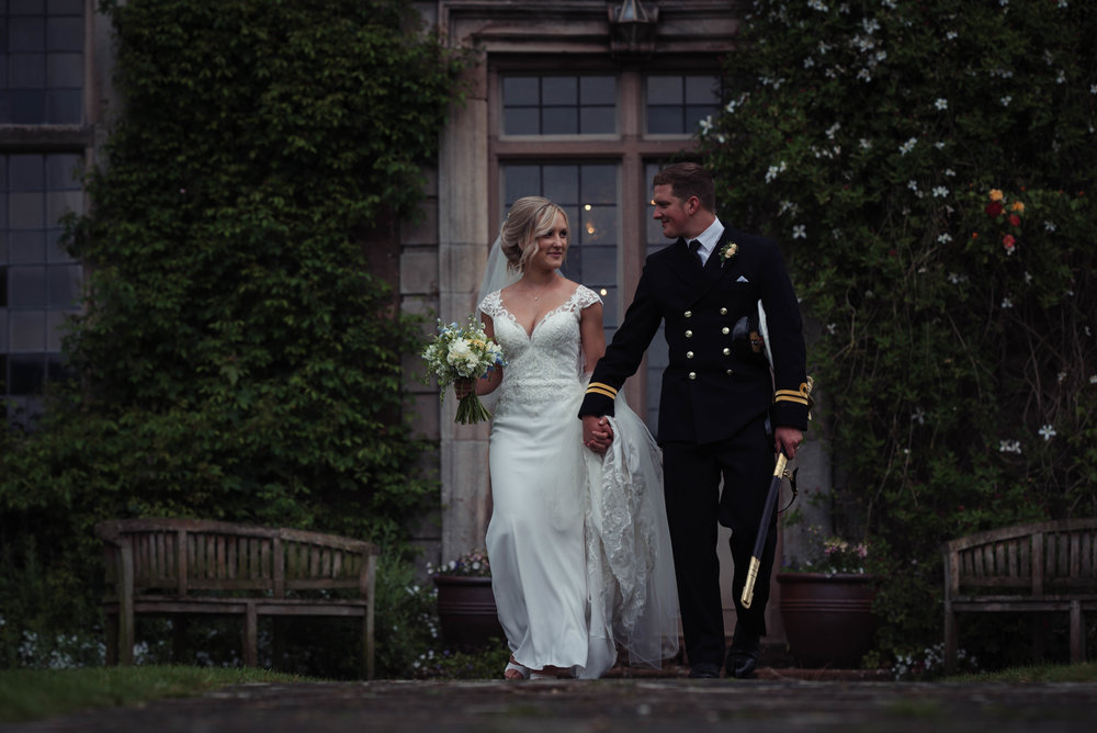 The bride in white and the royal navy groom have their wedding photography portraits outside Askham Hall
