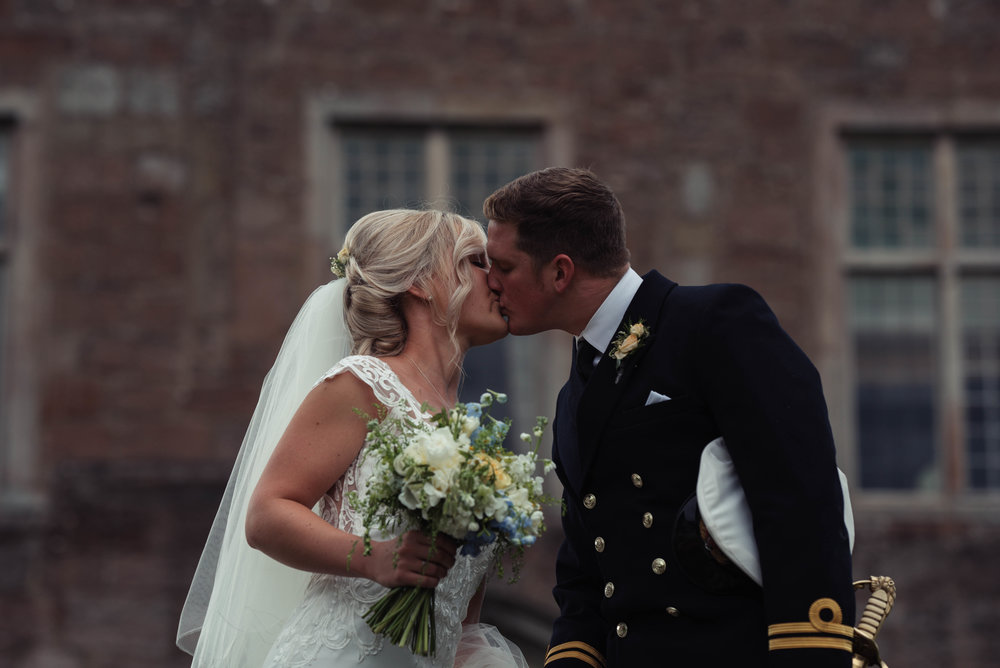 The bride and groom share a kiss outside Askham Hall