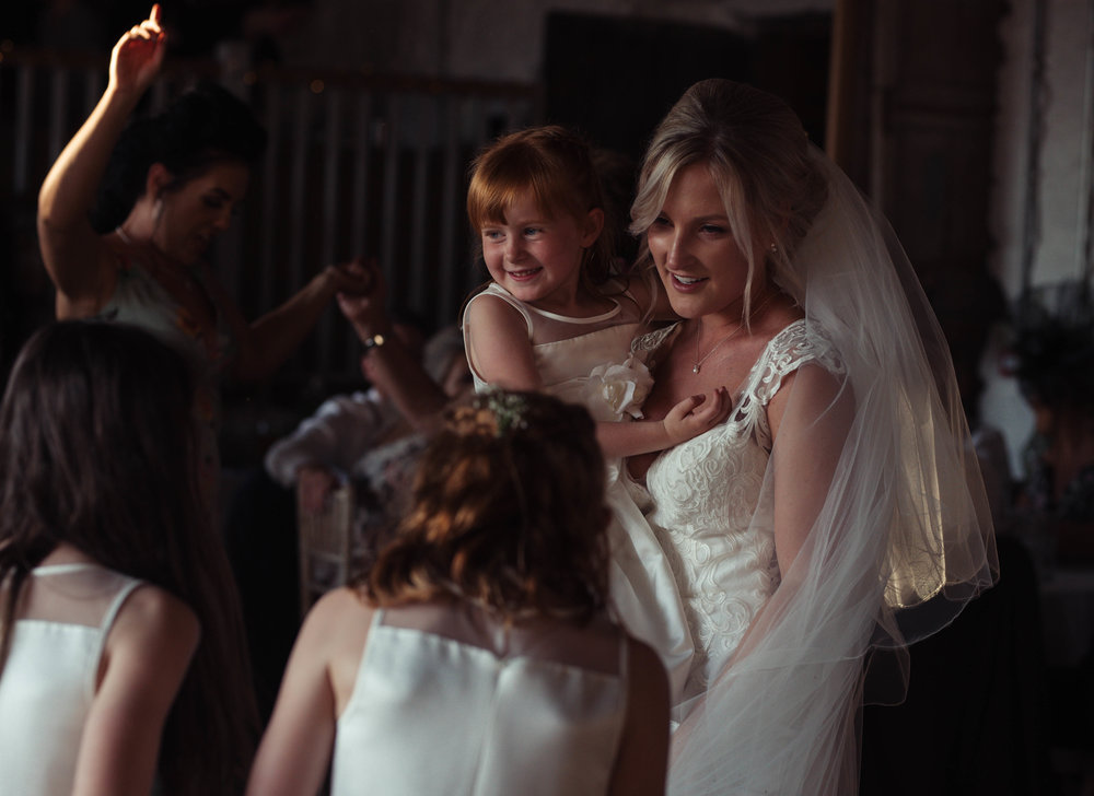 The bride holds a flower girl in her arms on the dance floor