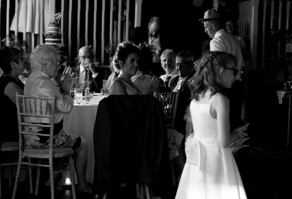 A bridemaid sits and smiles as she watches the first dance