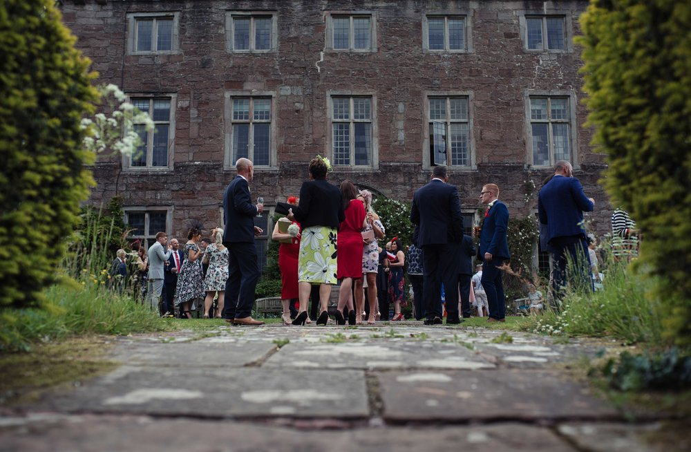 Guests gather outside Askham Hall for the wedding reception