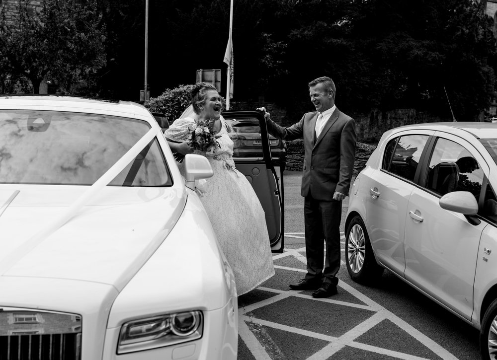 The bride arrives at kendal register office and laughs as she gets out of her white car
