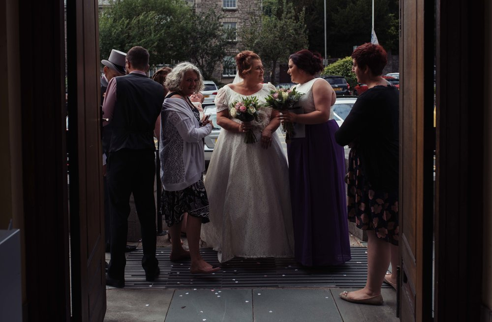 The bride and groom and wedding party gather outside the register office waiting to be invited in