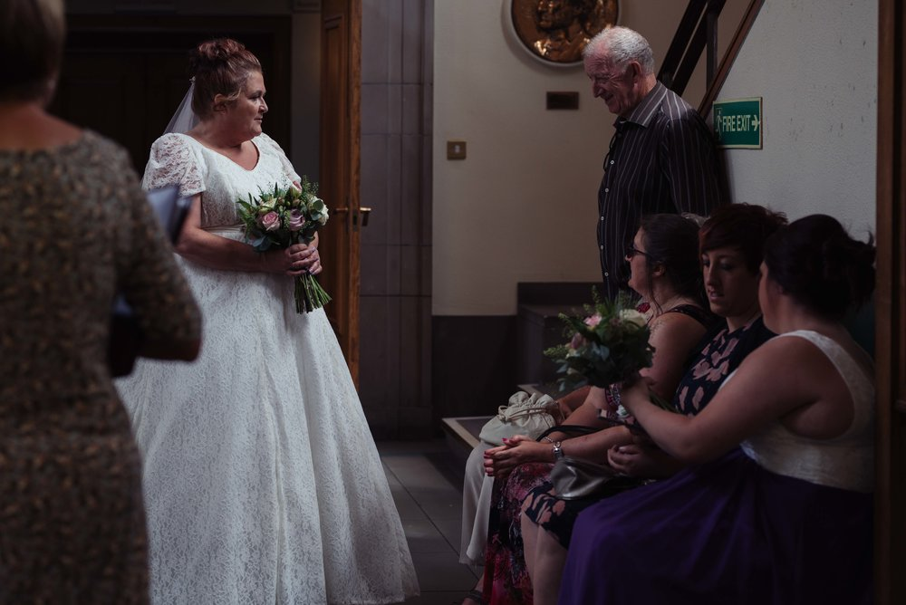 The bride chats to guests as she waits outside the wedding ceremony room