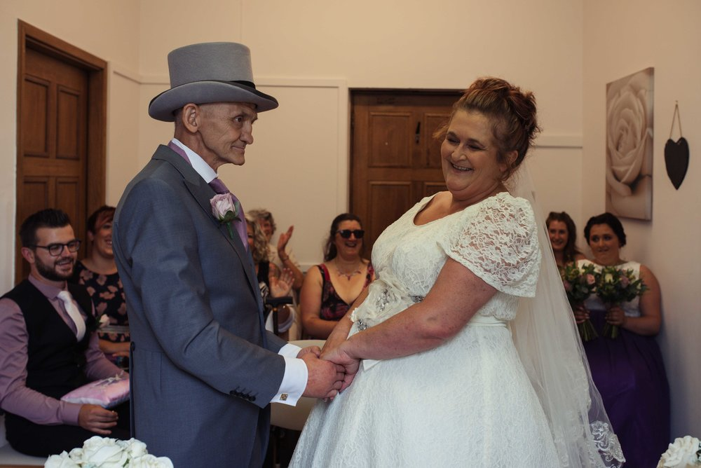 The groom makes the bride laugh as they stand holding hands during the wedding ceremony