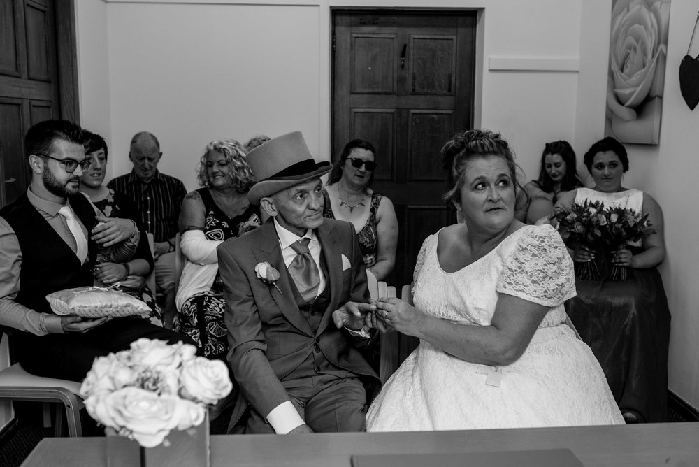 The bride and groom look towards the registrar as she speaks to them