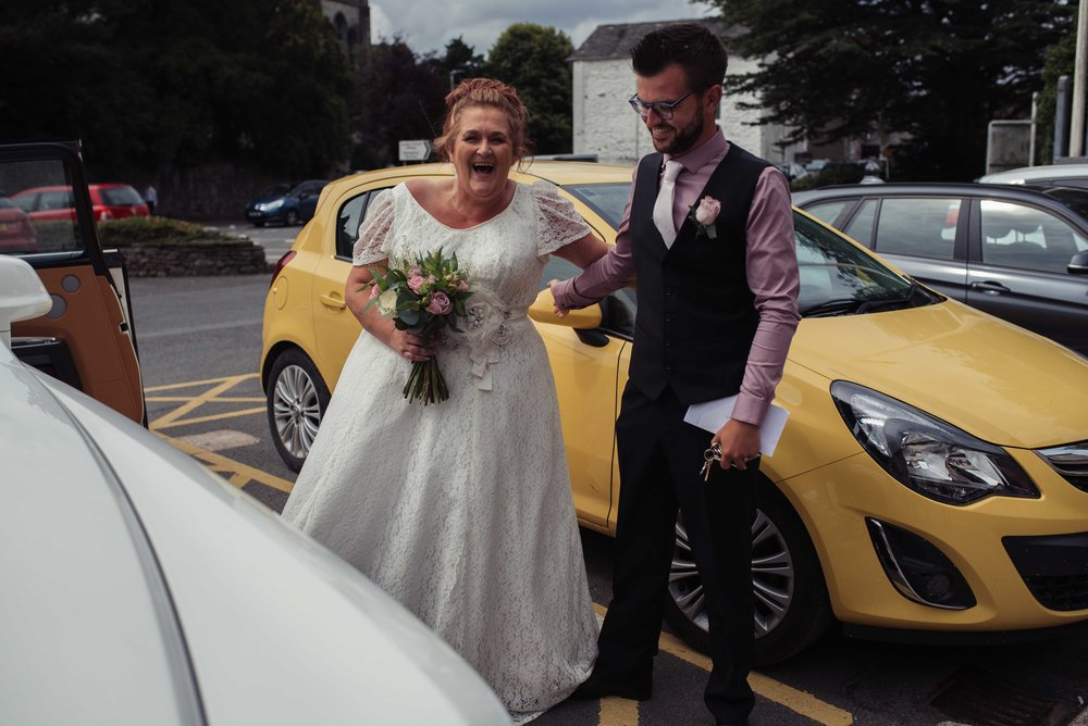 The bride and the best man have a laugh outside the wedding car