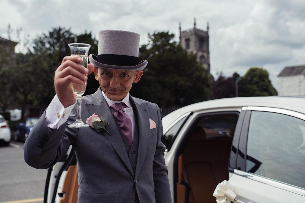 The groom raises a toast to the camera