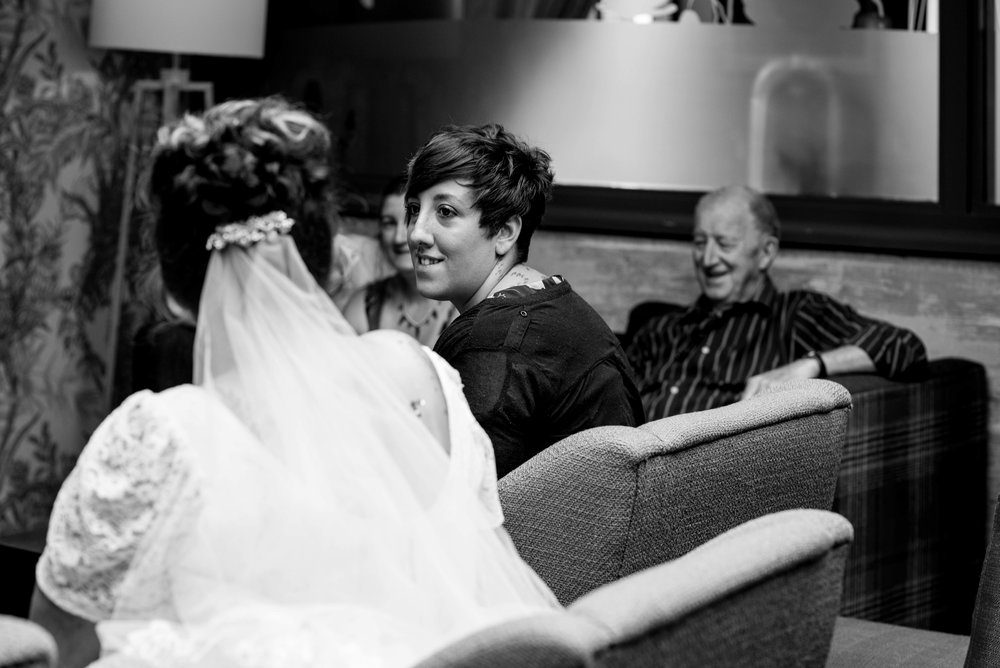 a short-haired wedding guest sits chatting to the bride