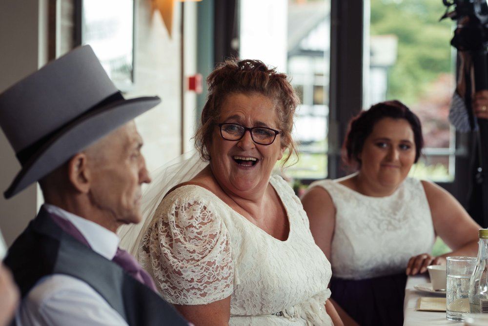 The bride looks to her new husband and laughs her head off