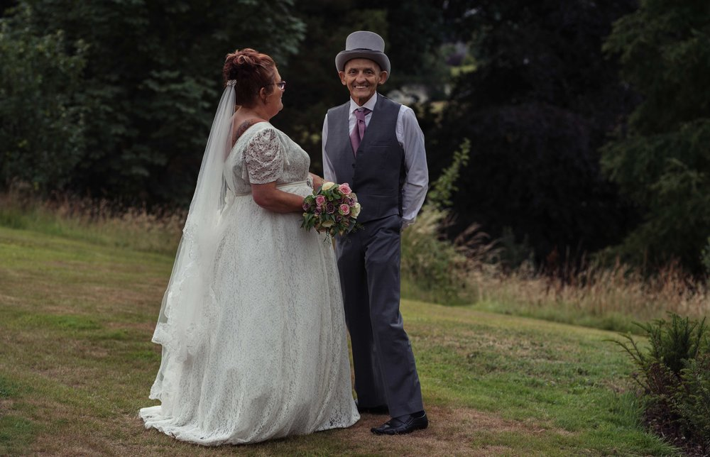 The groom giggles towards the camera as they stand for their Cumbria wedding photography
