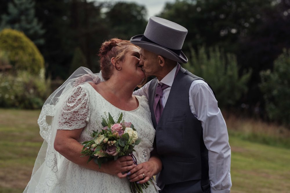 The bride and groom share a kiss together in the grounds of the castle green hotel