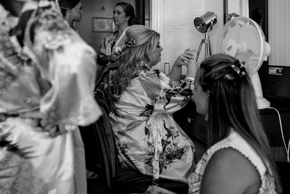 Bride and the inn on the lake sits to have her hair done whilst playing with her braclet