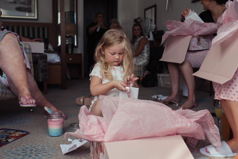A young flower girls looks at her presents off the bride
