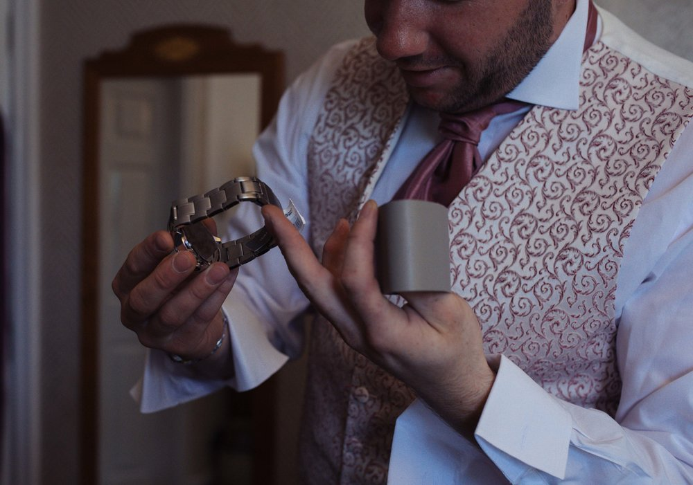 Close up of the groom looking at his watch, a present from his bride