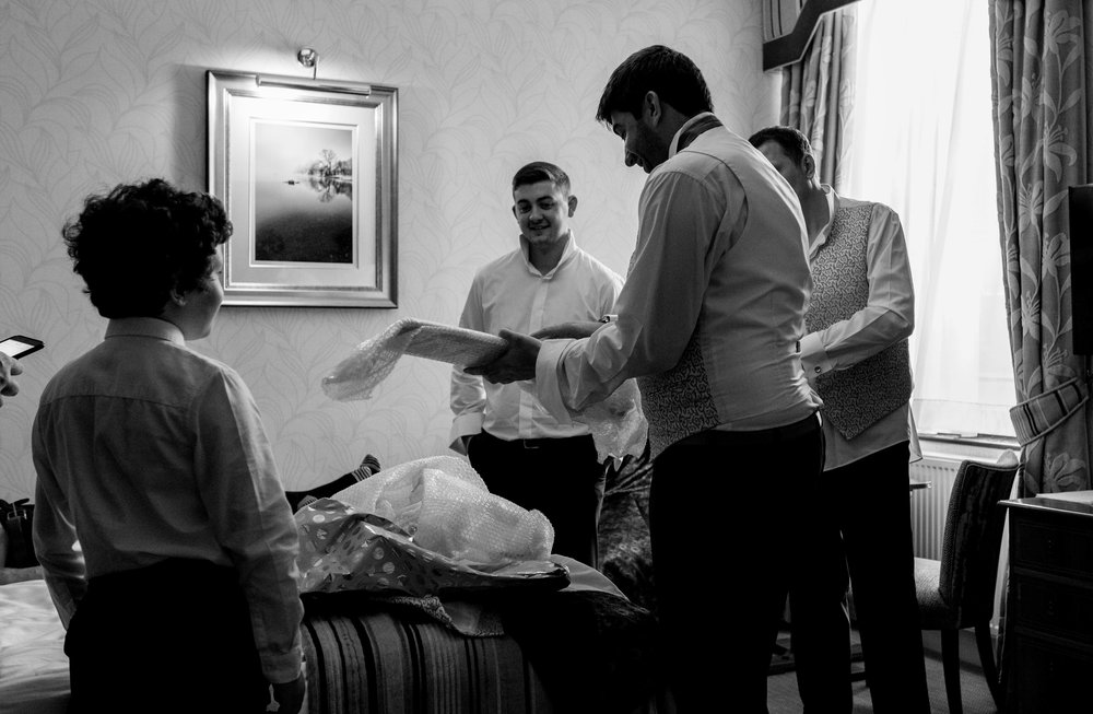 The groom opens his presents from the bride