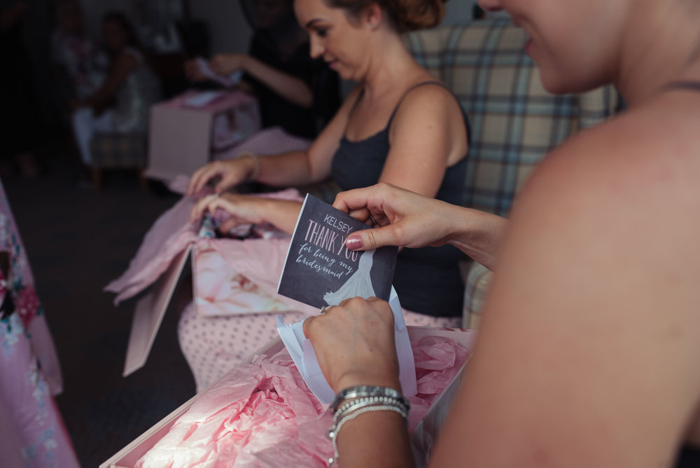 Bridesmaids open their presents from the bride