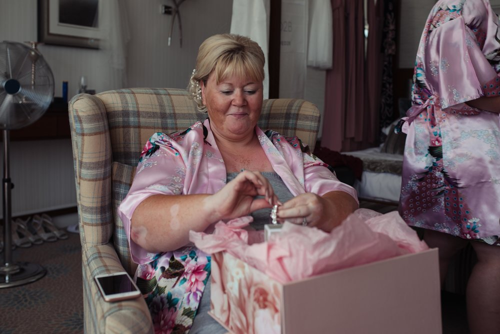 An emotional mother of the bride looks at her presents off her daughter