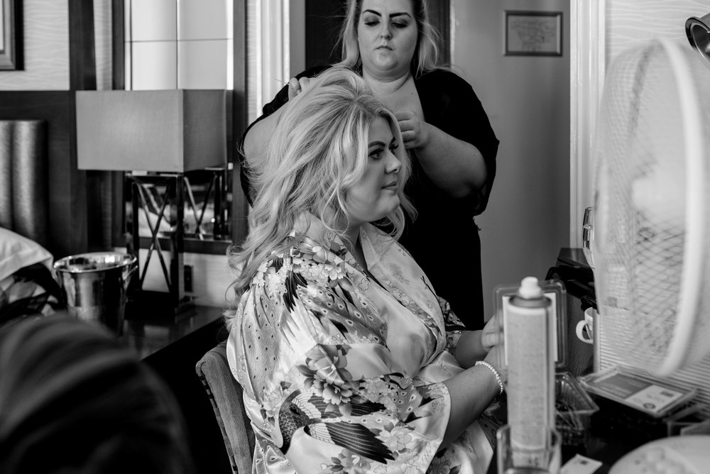 Bride in black and white looks into the mirror as she has her hair done