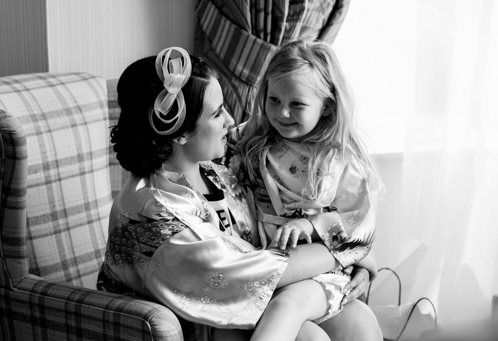 The flower girl and her auntie sitting together during bridal preps